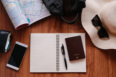 Notebook and travel accessories costumes on wood table background with text space.
