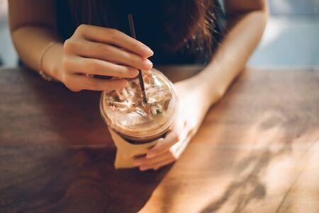 Main de femme tenant une tasse de café sur une vieille table en bois. Banque d'images - 84731931
