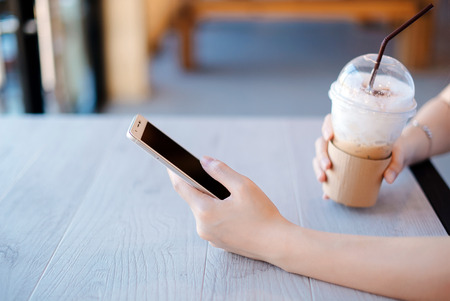 Young woman using smartphone during drink coffee a in coffee shop.