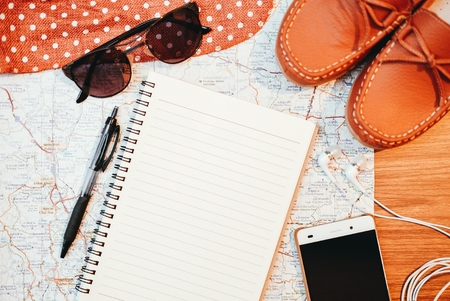 Notebook and travel accessories on wooden background.