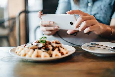 Hands of woman taking a photo of breakfast with smartphone.