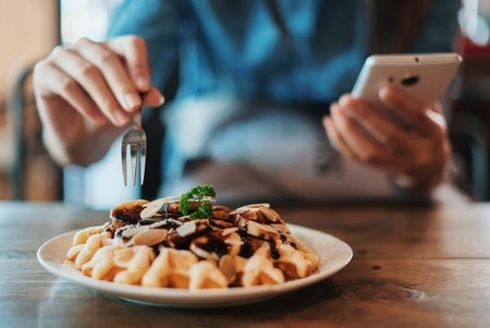 Hand of woman having breakfast and using on a mobile phone.