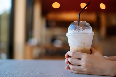 Hand of woman holding coffee cup on white table in coffee shop.