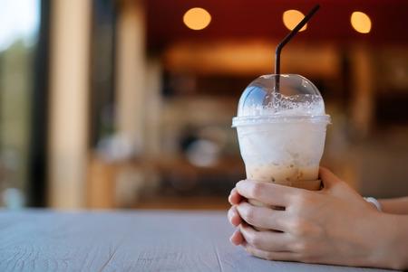 Main de femme tenant une tasse de café sur une table blanche dans un café. Banque d'images - 85181134