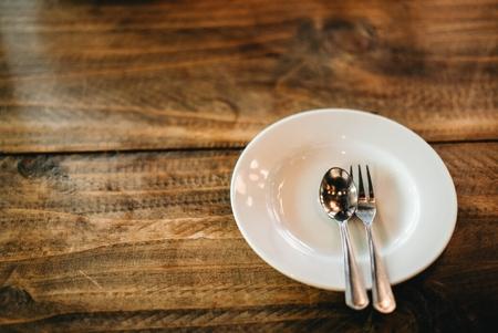 White plate on wooden table. Standard-Bild