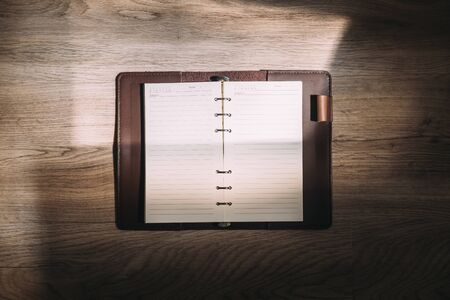 Top view of blank notebook on wooden desk in sunlight. Banque d'images - 133534091