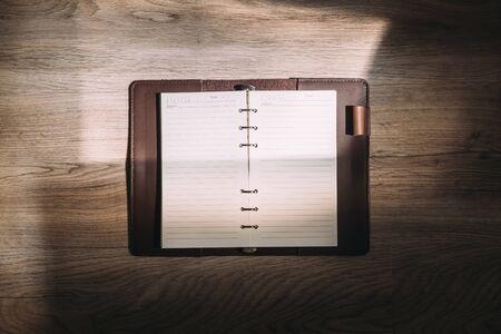 Top view of blank notebook on wooden desk in sunlight. Standard-Bild