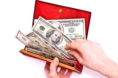 change purse: Dollars in red wallet and woman hands isolated on white