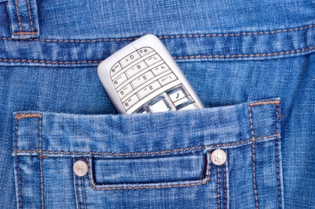Steel phone in back pocket of blue jeans. photo
