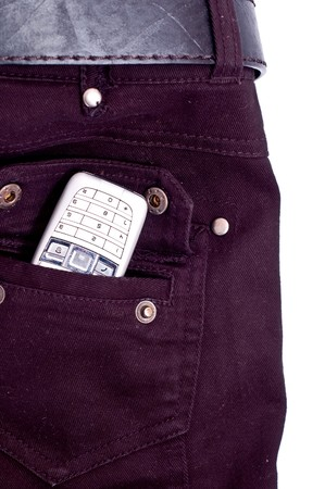 Cell phone in pocket of black jeans. photo