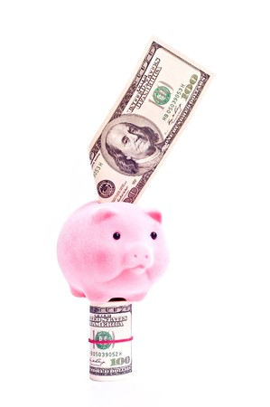 a pink pig stands on the dollars isolated on white Stock Photo - 7372407