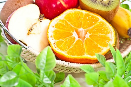 Fresh cut fruits in the basket with green leaves isolated on white photo