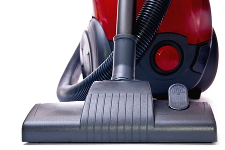 Modern red vacuum cleaner isolated on white background photo