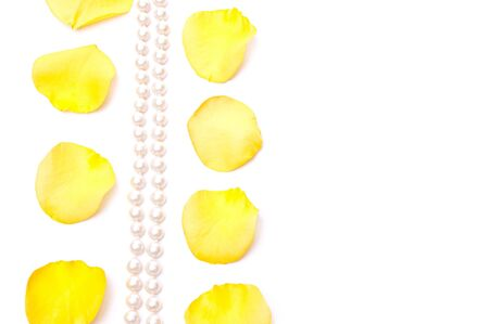 Yellow roses petals and white pearls isolated on white photo