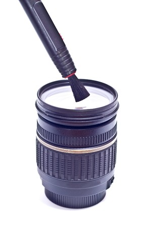neccessary: camera lens with lens cleaning brush pen on white background Stock Photo