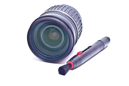 neccessary: a camera lens with lens cleaning brush pen isolated on white