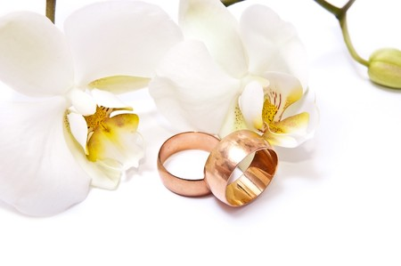 Gold rings with white orchid isolated on white background photo