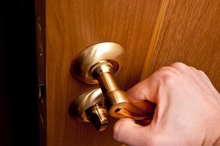 closing: Man hand opening door leading into dark room Stock Photo