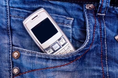 Cell phone in pocket of blue jeans. photo
