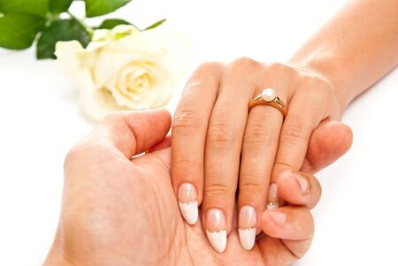 Man holding beautiful womans hand with ring. On white background photo