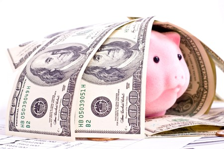 Pink pig in house from dollars isolated on white. Focus on dollars photo