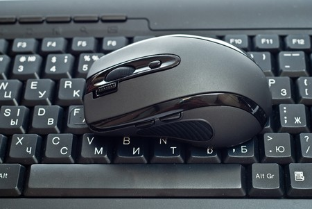 Black mouse on pc keyboard. Studio shot photo