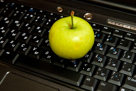 Computer keyboard and green apple close up photo