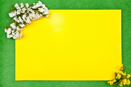 A blank yellow card with fresh flowers. Green background photo