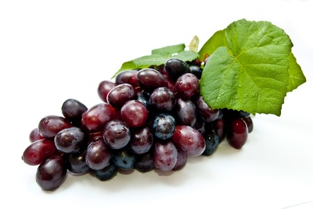 Fresh dark grape with leaves. Isolated on white photo