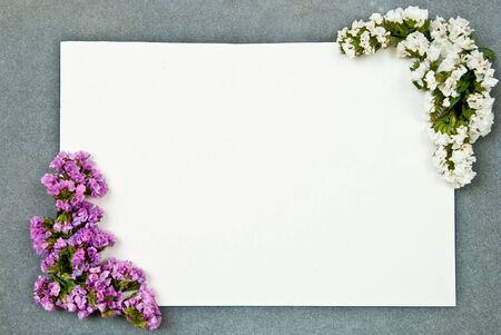 Green paper blank on grey background. With flowers photo