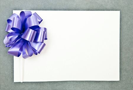 White paper blank with bow on grey background  photo