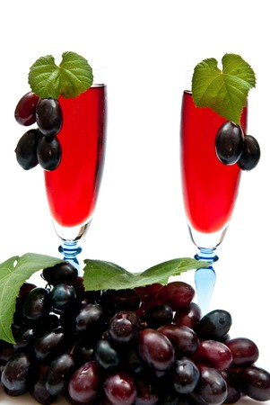 Red wine in glasses with plump grapes. Isolated on white photo