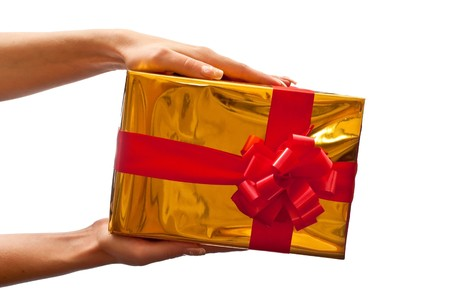 Womans hands with yellow gift box and red bow isolated on white background photo