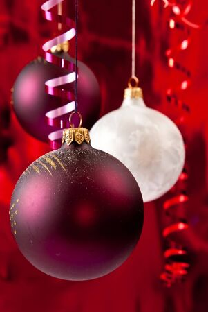Christmas baubles and ribbons on red background photo