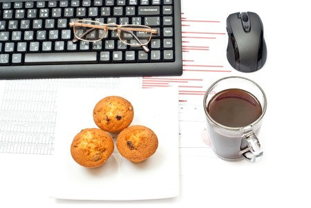 Business still-life with diagrams, glasses, coffee, cake and keyboard photo
