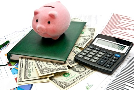 bank office: Piggy bank on office table with charts, money, calculatro and notebook