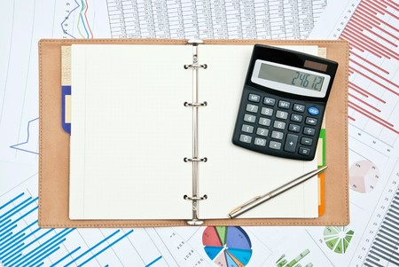 Financial charts with calculator,pen,notebook and pen photo