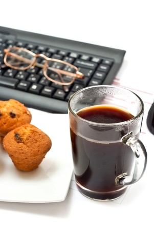 Hotc coffe, diagrams, keyboard, mouse and cakes on office table photo