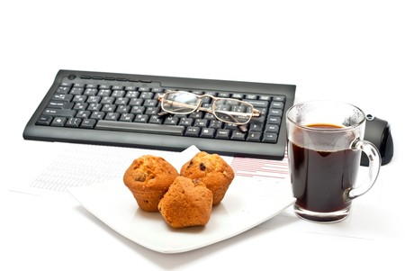Hotc coffe, diagrams, keyboard, mouse and cakes. photo