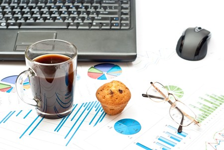 Business still-life with diagrams, glasses, coffee, cake and notebook photo