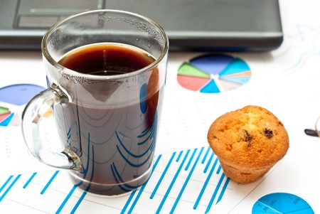 Close-up on stock market data charts, coffee and cake photo