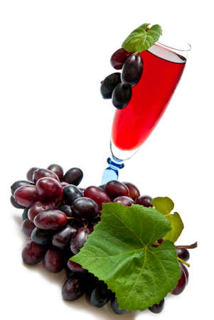 Red wine in glass with plump grapes. Isolated on white photo