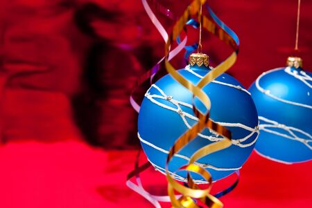 Christmas decoration from two blue balls on red background photo