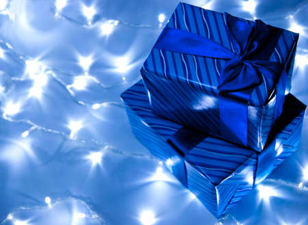 Two blue gifts boxes with garland background. Studio shot photo