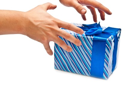 horozontal: Blue gift box with bow and mans hands. Isolated on white Stock Photo