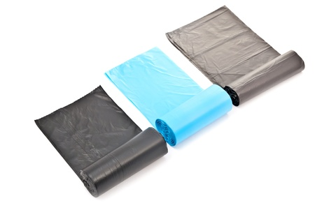 Black and blue rolled garbage bags. Isolated on white with soft shadow photo