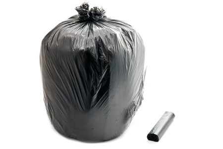 Tied black garbage bag isolated on a white background. photo