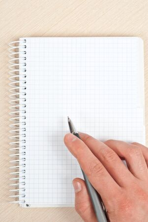 Male hand holding a pen writing notes in a notebook. photo