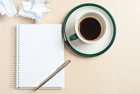 Pencil on a white notepad with cup of coffee on desk photo