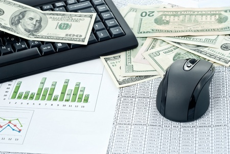 Black keyboard, mouse and dollars on a stock chart photo